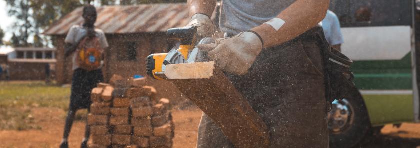 man sawing board village